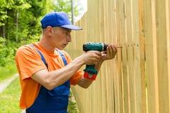 Handiman especializado que aperta os parafusos na placa de madeira Fotos de Stock Royalty Free