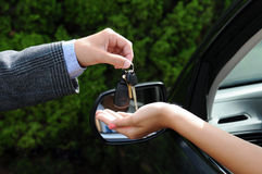 Handing 0ver Keys to New Car. Salesman handing over the keys to a new car. Closeup of the man's hand handing keys to the woman's hand sticking out the window of Royalty Free Stock Photos