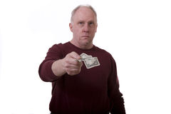 Handing a Dollar. An older man in a red shirt handing across a dollar bill on a white background Stock Images