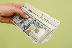 Handing a 100 dollar bill to viewer. On green background royalty free stock photo