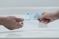Handing an euro banknote Stock Image