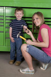 Handing hammer to boy. A mom and son getting ready to work by using just their size of hammers Stock Photos