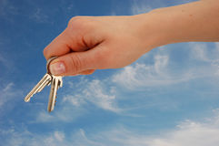 Handing with Keys against blue Stock Photo