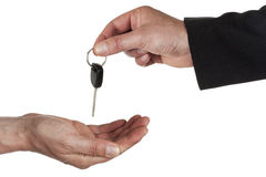 Handing out the car keys. Hand of man in business suit handing car key over to another hand Royalty Free Stock Photos