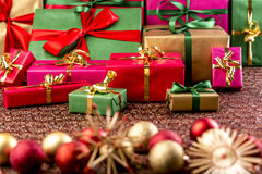 Handing Out of Christmas Gifts. Christmas gifts piled up for handing out of presents. Wrapped in green red, gold and magenta. Straw stars and Xmas ornaments Stock Photo