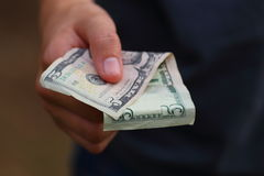 Handing out Money. Close up view of someone handing out money Stock Image