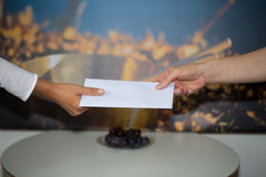 Handing out money envelope to employees. Woman hand Royalty Free Stock Photography