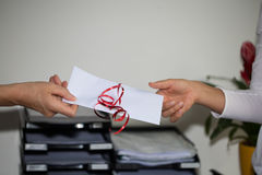 Handing out money envelope to staff , gratuity. In a office Royalty Free Stock Photography