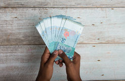 Handing out money in Malaysia ringgit Royalty Free Stock Image
