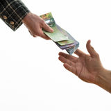 Handing Out Money. Woman hand handing Canadian money to a male hand. Over white background. Doing business between women and men Royalty Free Stock Images