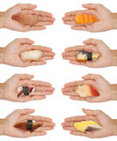Handing Out Sushi. 8 hands holding out various kinds of sushi/sashimi isolated on white Stock Photography