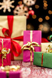 Handing Out of Xmas Presents. Tightly framed Christmas presents in red, green, magenta and golden colors. Sparkling orange light reflexes and blurry stars Royalty Free Stock Image