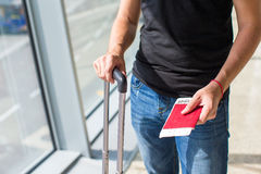Handing over boarding pass and passport to embark. Close up of man holding passports and boarding passport at airport royalty free stock images