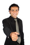 Handing Over Car Keys. A young Indian businessman handing over the keys of a new car to a customer, isolated on white studio background. (Focus on Hand Stock Image