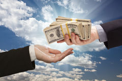 Handing Over Cash with Dramatic Clouds and Sky. Background Royalty Free Stock Photo