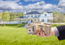 Handing Over Cash For House in Front of Home. Handing Over Cash For House in Front of Beautiful New Home Stock Photos