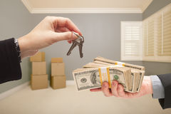 Handing Over Cash For House Keys. Man and Woman Handing Over Cash For House Keys Inside Empty Gray Room with Boxes Royalty Free Stock Image