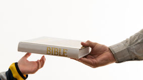 Handing over the faith. Handing over our belief. Old mand handing over a Bible to a new generation. Hand of a young kid receiving an old education. Handing over Royalty Free Stock Photography
