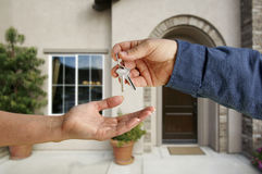 Handing Over the House Keys in Front of New Home Stock Images