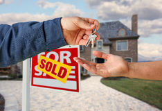 Handing Over the House Keys in Front of New Home Royalty Free Stock Photography