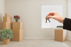 Handing Over House Keys In Room with Packed Moving Boxes Royalty Free Stock Image
