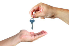 Handing over the keys. A male's hand giving a key to another male's hand Stock Photo