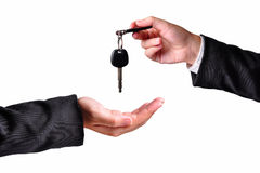 Handing over the keys. A hand giving a key to another hand. Both persons in suits. Isolated Stock Photo