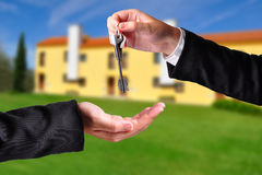 Handing over the keys. A hand giving a key to another hand. Both persons in suits. House in the background Stock Photo