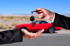 Handing over the keys. A hand giving a key to another hand. Both persons in suits. Car in the background Royalty Free Stock Images