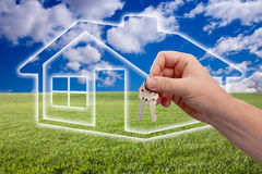 Handing Over Keys on Ghosted Home Icon and Field. Male Handing Over Keys on Ghosted Home Icon, Grass Field, Clouds and Sky Royalty Free Stock Photos