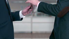 Handing over the keys and handshake. Young guy buying a car from a dealer. Handshake between buyer and seller. Car seller hands over the keys to the buyer in car stock footage