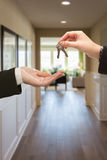 Handing Over The Keys Inside House. Woman Handing Over The Keys Inside Hallway of New House Royalty Free Stock Image