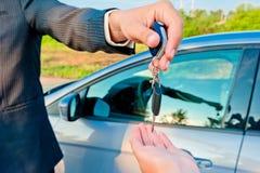 Handing over keys of new car buyer Stock Photos