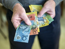 Handing over the money. A man paying cash for his purchase in Australian dollars. Copyspace stock photos