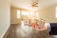 Handing Over Thousands of Dollars In Empty Room of House. Handing Over Thousands of Dollars In Empty Room of a New House royalty free stock photo