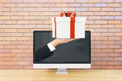 Handing present from screen Stock Photos
