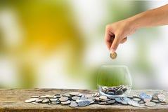 Handinnehav som sätter myntet in i klart exponeringsglas på trätabellen Royaltyfri Bild