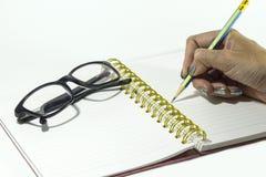 Handinnehavblyertspenna på anteckningsboken med svarta exponeringsglas Royaltyfria Bilder
