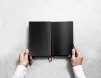 Handinnehavmellanrumet öppnade upp bokåtlöje med svarta sidor fotografering för bildbyråer