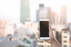 Handinnehavsmartphone eller mobiltelefon med stadsbyggnadsbakgrund och kopieringsutrymme royaltyfria foton