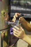 Handjongen die het glas met water van de waterkoeler houden stock foto's