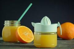 Handjuicer voor sinaasappelen Dichtbij is een kruik met vers gedrukt jus d'orange royalty-vrije stock afbeeldingen