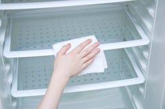 Handkaukasisches Mädchen mit einem weißen Lappen wäscht den Kühlschrank lizenzfreie stockfotografie