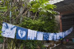 Handkerchief tie batik dyeing tie batik indigo color. Or mauhom color and hanging process dry clothes in the sun at garden outdoor in Nonthaburi, Thailand royalty free stock photography
