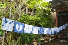 Handkerchief tie batik dyeing tie batik indigo color. Or mauhom color and hanging process dry clothes in the sun at garden outdoor in Nonthaburi, Thailand stock photo