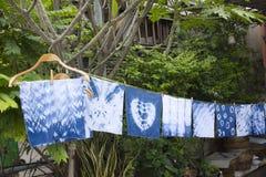 Handkerchief tie batik dyeing tie batik indigo color. Or mauhom color and hanging process dry clothes in the sun at garden outdoor in Nonthaburi, Thailand royalty free stock photo
