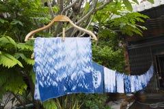 Handkerchief tie batik dyeing tie batik indigo color. Or mauhom color and hanging process dry clothes in the sun at garden outdoor in Nonthaburi, Thailand stock photos