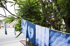 Handkerchief tie batik dyeing tie batik indigo color. Or mauhom color and hanging process dry clothes in the sun at garden outdoor in Nonthaburi, Thailand stock image