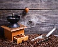 Handkoffiemolen met bonen en uitstekende lepel op houten achtergrond royalty-vrije stock afbeeldingen
