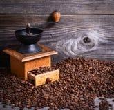 Handkoffiemolen met bonen op houten achtergrond stock foto's